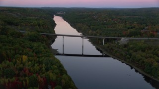 AX149_239 - 6K stock footage aerial video approaching small bridge spanning Kennebec River, autumn, Augusta, Maine, twilight