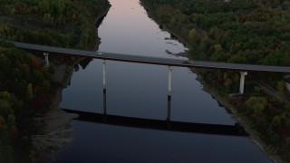 AX149_240 - 6K stock footage aerial video approaching and flying over small bridge, Kennebec River, autumn, Augusta, Maine, twilight