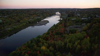 AX149_243 - 6K stock footage aerial video flying over colorful forest, approach Kennebec River, autumn, Augusta, Maine, twilight