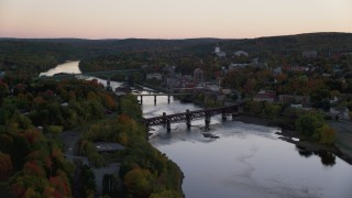 AX149_245 - 6K stock footage aerial video flying by small bridge, Kennebec River, downtown, autumn, Augusta, Maine, twilight