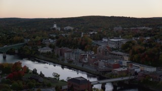 AX149_247 - 6K stock footage aerial video flying by downtown in autumn, small bridges, Kennebec River, Augusta, Maine, twilight