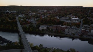 AX149_248 - 6K stock footage aerial video flying by small bridges into downtown, Kennebec River, Autumn, Augusta, Maine, twilight