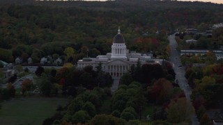 AX149_250 - 6K stock footage aerial video flying by dense trees surrounded Maine State House, autumn, Augusta, Maine, twilight