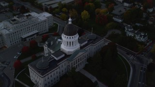 AX149_253 - 6K stock footage aerial video approaching Maine State House, tilt to bird's eye view, autumn, Augusta, Maine, twilight
