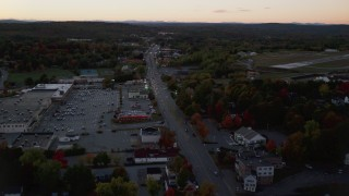 AX149_254 - 6K stock footage aerial video approaching Western Avenue strip mall in autumn, Augusta, Maine, twilight