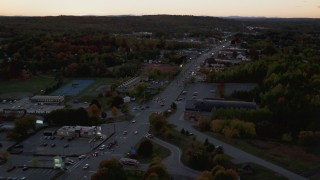 AX149_255 - 6K stock footage aerial video flying by strip mall, Western Avenue, autumn, Augusta, Maine, twilight