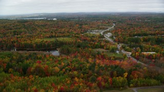 AX150_002 - 6K stock footage aerial video flying over forest, reveal cemetery, Western Avenue, autumn, Manchester, Maine