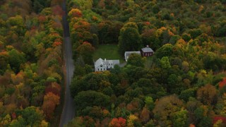 AX150_004 - 6K stock footage aerial video flying by an isolated home, colorful forest, autumn, Manchester, Maine