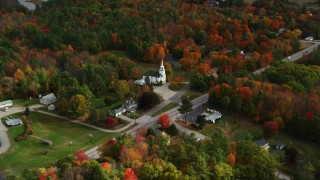 AX150_009 - 6K stock footage aerial video flying by East Winthrop Baptist Church, colorful foliage, autumn, Winthrop, Maine