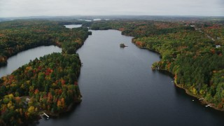 AX150_011 - 6K stock footage aerial video flying by Upper Narrows Pond, dense forest in autumn, Winthrop, Maine