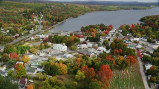 AX150_015 - 6K stock footage aerial video flying by a small town, school, sports fields, autumn, Winthrop, Maine