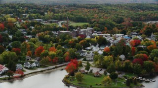 AX150_019 - 6K stock footage aerial video flying by small town near the water, homes, factory, autumn, Winthrop, Maine