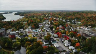 AX150_021 - 6K stock footage aerial video flying over small town homes, Main Street, tilt down, autumn, Winthrop, Maine