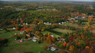 AX150_026 - 6K stock footage aerial video flying over rural homes, colorful foliage, tilt down, Monmouth, Maine