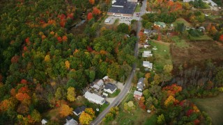 AX150_027 - 6K stock footage aerial video flying by rural homes, Main Street, tilt down over colorful foliage, autumn, Monmouth, Maine