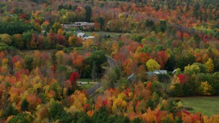 AX150_028 - 6K stock footage aerial video flying by country road, colorful forest, autumn, Monmouth, Maine