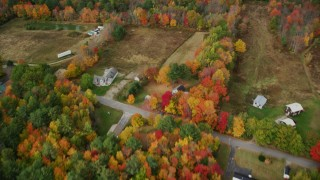 AX150_029 - 6K stock footage aerial video of a bird's eye view over colorful forest, reveal rural homes, autumn, Monmouth, Maine