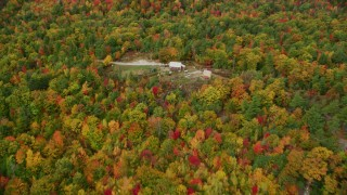 AX150_033 - 6K stock footage aerial video flying over colorful forest, approach isolated home, tilt down, autumn, Leeds, Maine