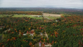 AX150_034 - 6K stock footage aerial video flying over colorful trees, approaching a farm, autumn, Leeds, Maine