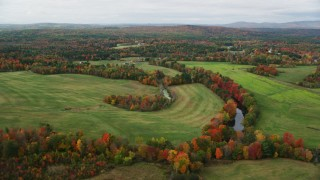 AX150_041 - 6K stock footage aerial video flying by Nezinscot River, colorful trees, green fields, autumn, Turner, Maine