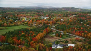 AX150_042 - 6K stock footage aerial video flying by a small rural town, colorful foliage in autumn, Turner, Maine