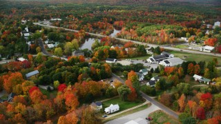 AX150_043 - 6K stock footage aerial video orbiting small rural town, colorful foliage in autumn, Turner, Maine