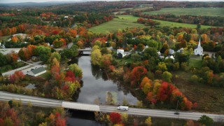 AX150_045 - 6K stock footage aerial video orbiting rural town, small bridges, Nezinscot River, autumn, Turner, Maine