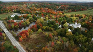 AX150_046 - 6K stock footage aerial video orbiting a small town, church, colorful foliage in autumn, Turner, Maine