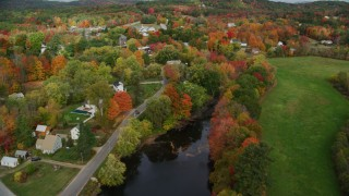 AX150_048 - 6K stock footage aerial video orbiting small rural town, colorful trees, Nezinscot River, autumn, Turner, Maine
