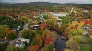 AX150_049 - 6K stock footage aerial video orbiting small rural town, bridges spanning Nezinscot River, autumn, Turner, Maine