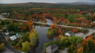 AX150_050 - 6K stock footage aerial video approaching small bridges spanning Nezinscot River, Auburn River, autumn, Turner, Maine