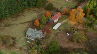 AX150_053 - 6K stock footage aerial video flying by an old barn, colorful foliage in autumn, Turner, Maine