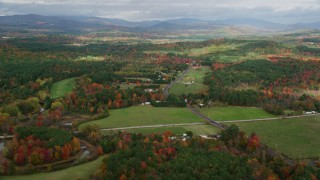 AX150_056 - 6K stock footage aerial video flying by colorful first, Turner Street, rural homes, autumn, Buckfield, Maine