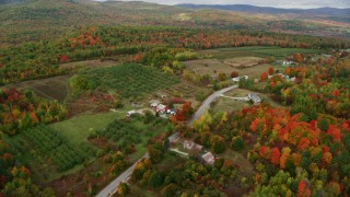 AX150_058 - 6K stock footage aerial video flying over colorful forest, approaching Hill Road, autumn, Buckfield, Maine