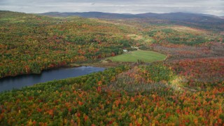AX150_059 - 6K stock footage aerial video flying over forest, approach isolated home near South Pond, autumn, Buckfield, Maine