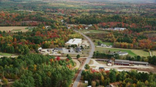 AX150_062 - 6K stock footage aerial video flying over real homes, colorful trees, Depot Street, autumn, Buckfield, Maine