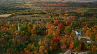 AX150_065 - 6K stock footage aerial video orbiting small town, rural homes, brightly colored foliage, autumn, Buckfield, Maine