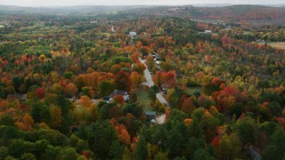 AX150_067 - 6K stock footage aerial video flying over small town, rural homes and Union Church, autumn, Buckfield, Maine