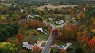 AX150_070 - 6K stock footage aerial video flying over small town, rural homes, Turner Street, colorful trees, autumn, Buckfield, Maine
