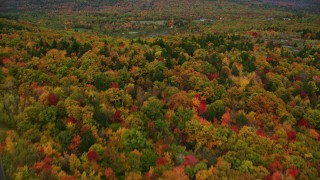 AX150_073 - 6K stock footage aerial video flying over colorful forest, tilt up, reveal rural residential area, autumn, Paris, Maine
