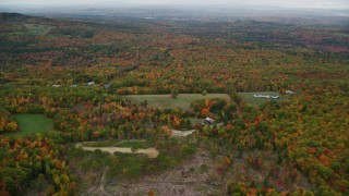AX150_074 - 6K stock footage aerial video flying over rural homes, approaching colorful forest, autumn, Paris, Maine