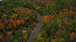 AX150_079 - 6K stock footage aerial video flying over colorful forest, tilt down on Buckfield Road, autumn, Paris, Maine
