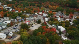 AX150_087 - 6K stock footage aerial video orbiting small rural town with colorful foliage, autumn, Paris, Maine