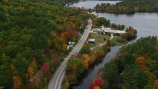 AX150_098 - 6K stock footage aerial video flying over rural homes near Lake Road, autumn, Norway, Maine