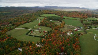 AX150_104 - 6K stock footage aerial video approaching small farms, colorful trees in autumn, pan right, Norway, Maine