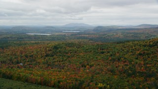 AX150_109 - 6K stock footage aerial video flying by forest of colorful trees in autumn on an overcast day, Norway, Maine