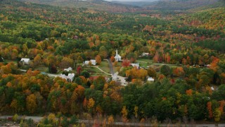 AX150_117 - 6K stock footage aerial video orbiting small rural town, dense forest in autumn, Waterford, Maine