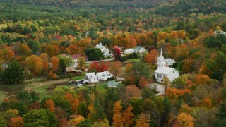 AX150_119 - 6K stock footage aerial video orbiting a small rural town, revealing a church, autumn, Waterford, Maine