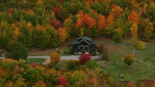 AX150_125 - 6K stock footage aerial video flying by an isolated rural home, colorful forest, autumn, Waterford, Maine