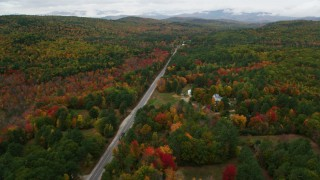 AX150_126 - 6K stock footage aerial video flying over rural homes, Main Street, colorful forest in autumn, Stoneham, Maine